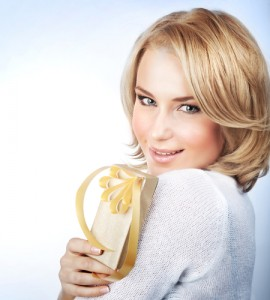Closeup photo of a beautiful young blonde-haired woman holding a gold-colored wrapped present