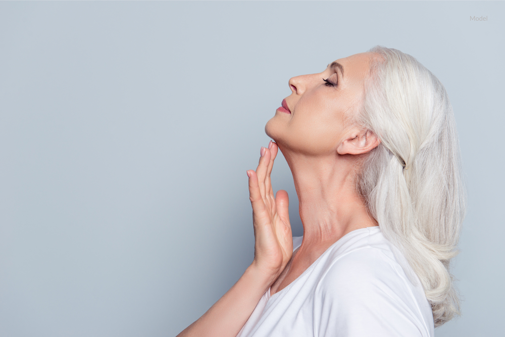 Woman caressing her neck. Neck lift concept.